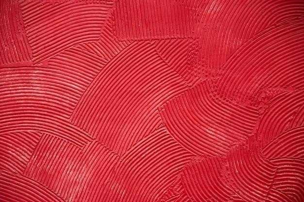 Muurtextuur met diepe cirkelvormige watten van stopverf, bedekt met rode verf.
