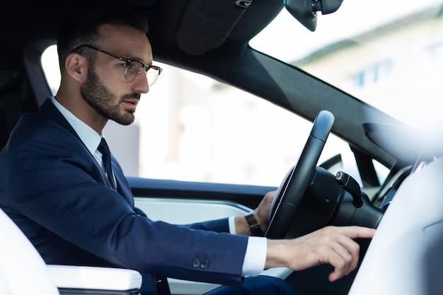 Muziek aanzetten. bebaarde knappe man met een bril die muziek aanzet terwijl hij in zijn auto rijdt
