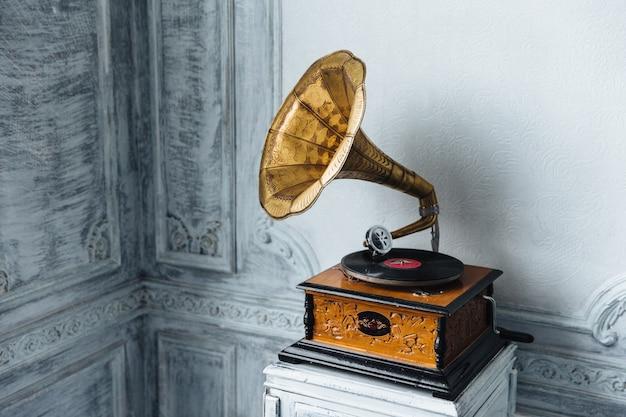 Muziek apparaat. oude grammofoon met plaat of vinylschijf op houten doos. antieke koperen platenspeler