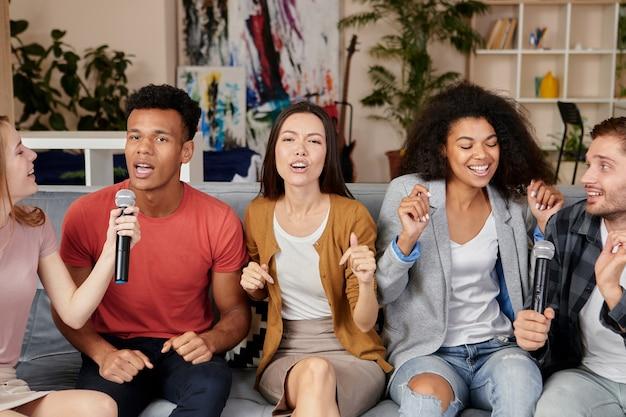 Muziek brengt vreugde enthousiaste multiculturele vrienden die zingen met microfoon tijdens het spelen van karaoke