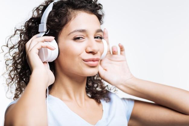 Muziek brengt vreugde. mooie curly-haired jonge vrouw die aan de muziek in hoofdtelefoons op wihte luistert