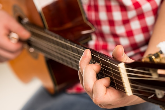 Muziek, close-up. muzikant die een houten gitaar houdt