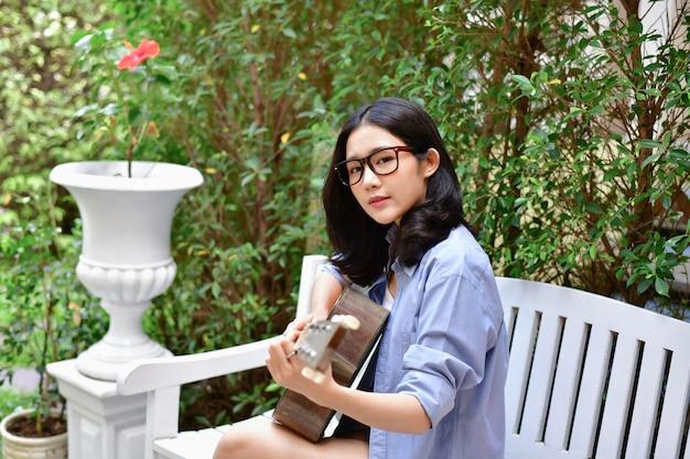 Muziek concepten. aziatische meisjes gitaar spelen. aziatische vrouwen die met muziek ontspannen.