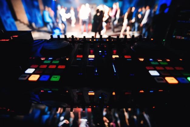Muziek dj desk met vage dansvloer met dansende mensen in nachtclub