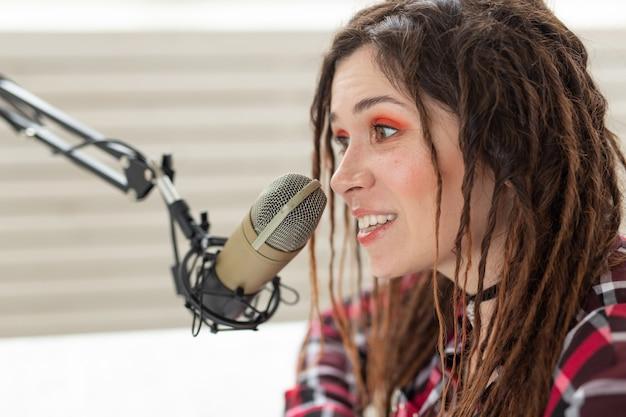 Muziek, dj en mensenconcept - jonge vrouw die bij de radio werkt