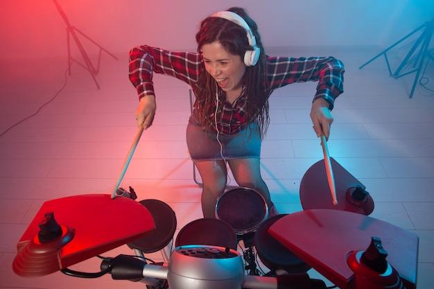 Muziek, drum en hobby concept - jonge vrouw het elektronische drumstel spelen in de club
