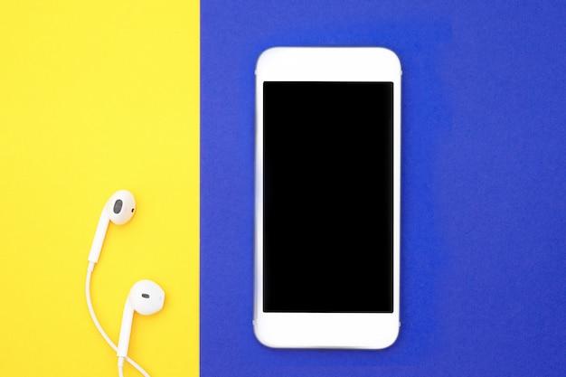 Muziek, gadgets, muziekliefhebber. witte smartphone en koptelefoon op gele en blauwe achtergronden met koptelefoon
