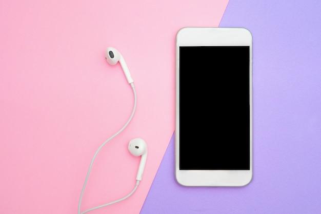 Muziek, gadgets, muziekliefhebber. witte smartphone op de paarse en blauwe achtergrond met koptelefoon. uitzicht van boven. plat lag, bovenaanzicht