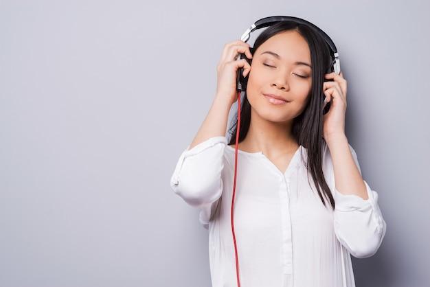 Muziek golven. mooie jonge aziaat in koptelefoon die ogen gesloten houdt en glimlacht terwijl hij tegen een grijze achtergrond staat