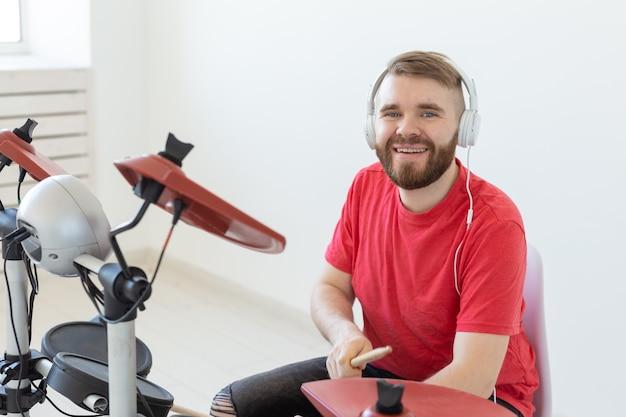 Muziek, hobby en mensen concept - jonge man drummer elektronische drums spelen