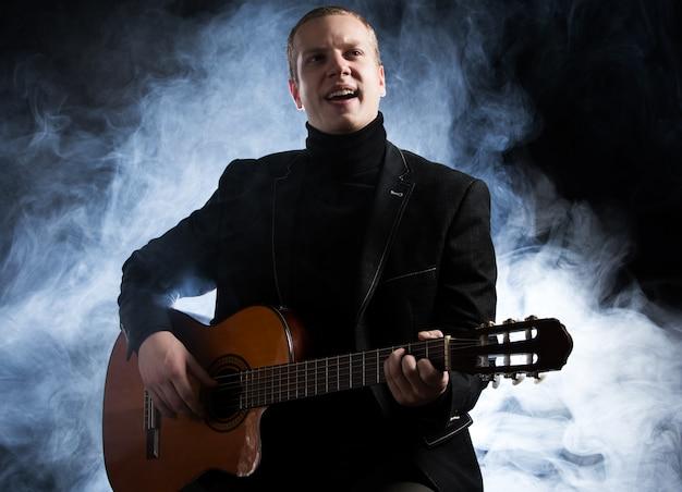 Muziek. jonge muzikant in zwart pak met een gitaar