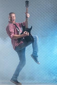Muziek. jonge muzikant met een gitaar op hek muur