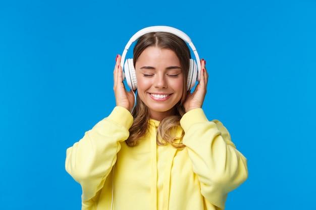 Muziek, levensstijl en jeugdconcept. close-upportret van dromerig gelukkig en ontspannen jong blond europees meisje sluit ogen en genietend van fijn geluid van lied in hoofdtelefoons, dromend,