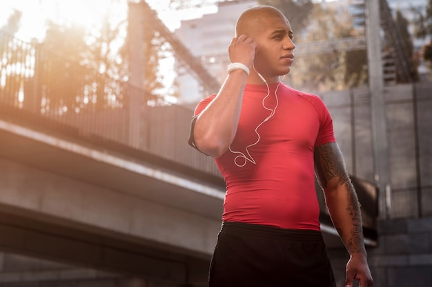 Muziek liefhebber. knappe afro amerikaanse man met een witte koptelefoon terwijl hij naar muziek wil luisteren