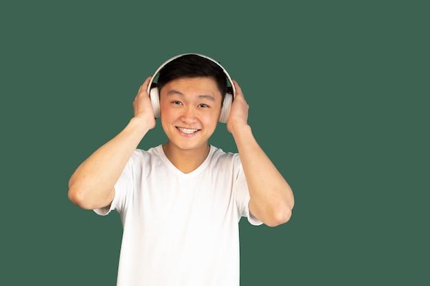 Muziek luisteren. aziatische jonge man portret op groene muur. knap mannelijk model in casual stijl. concept van menselijke emoties, gezichtsuitdrukking, jeugd, verkoop, advertentie.