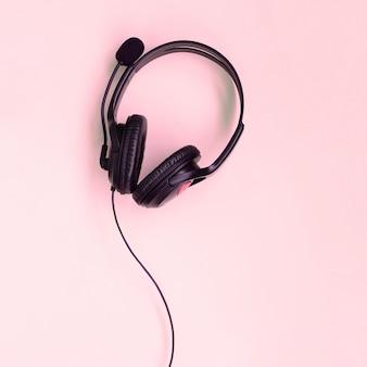 Muziek luisteren concept. zwarte koptelefoon ligt op roze