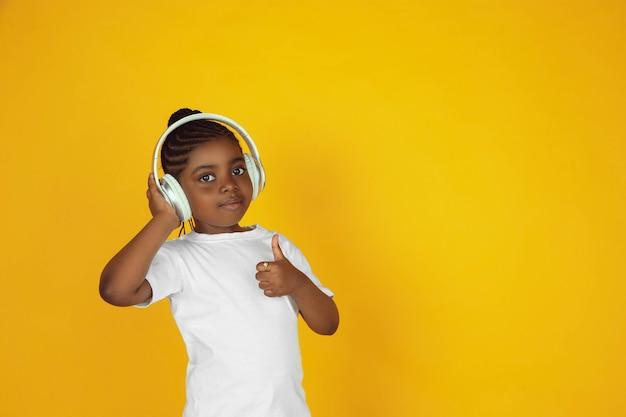 Muziek luisteren met een koptelefoon. het portret van een klein afrikaans-amerikaans meisje dat op gele studioachtergrond wordt geïsoleerd. concept van menselijke emoties, gezichtsuitdrukking, verkoop, advertentie. kopieerruimte. ziet er schattig uit.