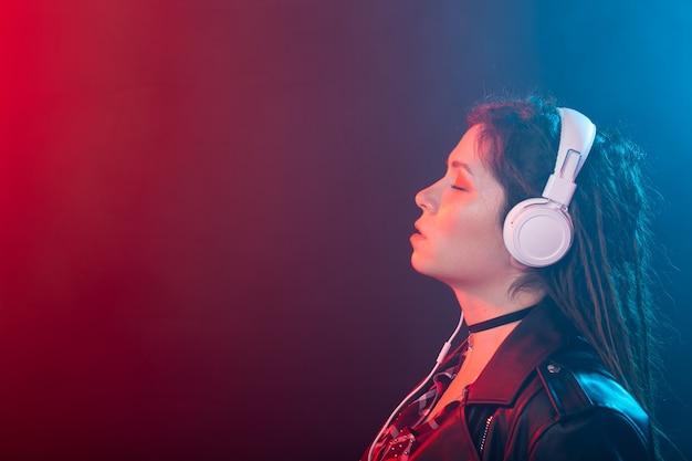 Muziek, meloman en mensenconcept - een gelukkige vrouw met dreadlock die naar muziek luistert en ervan geniet