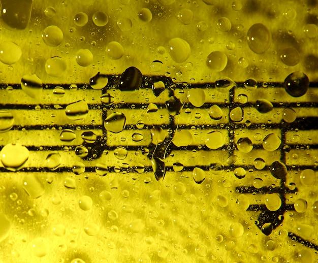 Muziek notities over glas overspoeld met druppels met een gele achtergrond