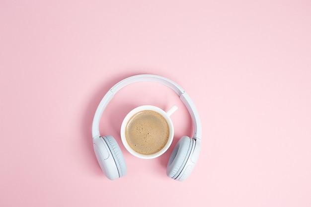 Muziek of podcast concept met koptelefoon en kopje koffie op roze tafel. bovenaanzicht, plat gelegd