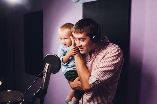 Muziek, showzaken, mensen en stemconcept - mannelijke zanger met hoofdtelefoons en microfoon het zingen lied bij geluidsopnamestudio.