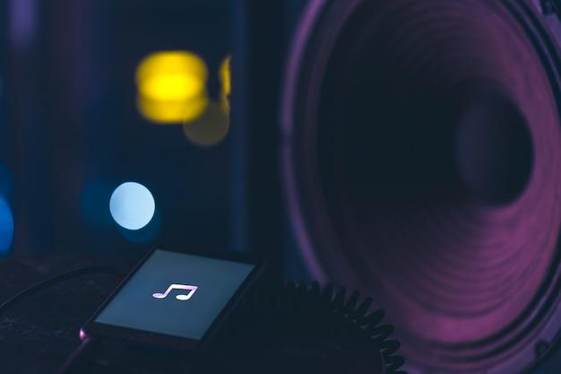 Muziekachtergrond met telefoon en met muziekpictogram en kolom, modern technologieconcept, luisterend naar muziek.