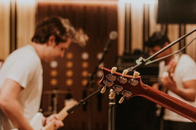 Muziekbandgitarist die herhaling uitvoert in opnamestudio