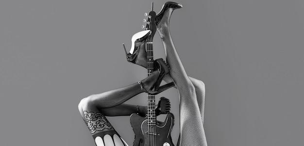 Muziekconcept. sexy benen. gitaar, elektrische gitaar. muziekfestival, live muziek, concert. instrument op het podium en band. fetisj, sexy vrouw, elektrische gitaar en benen, ondergoed. fetisj lingerie