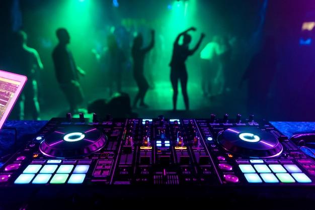Muziekcontroller dj in de stand vlakbij de dansvloer