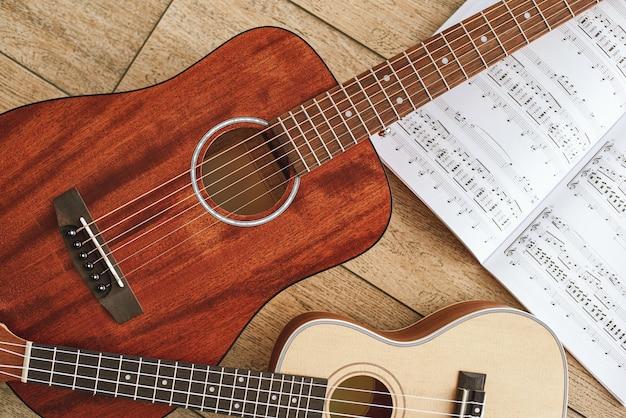 Muziekeducatie bruine akoestische gitaar en ukelele liggend op de houten vloer met muzieknoten