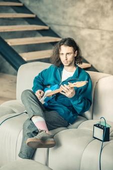 Muziekinstrument afstemmen. serieuze knappe muzikant in blauwe top zittend op de grijze bank met gitaar en versterker