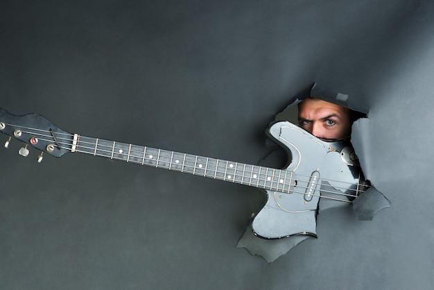 Muziekinstrument. mannelijk gezicht kijk door papier. elektrische gitaar door gescheurd zwart papier. man komt uit gat in papieren muur met elektrische gitaar. kopieer ruimte voor het adverteren van muziekinstrumenten in de winkel