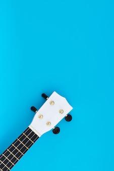 Muziekinstrument op een blauwe achtergrond. de witte ukelele is op een blauwe achtergrond. plat lag patroon