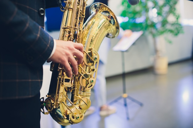 Muziekinstrumenten, saxofonist overhandigt saxofonist die jazzmuziek speelt. close-up van het altsaxofoon de muzikale instrument.