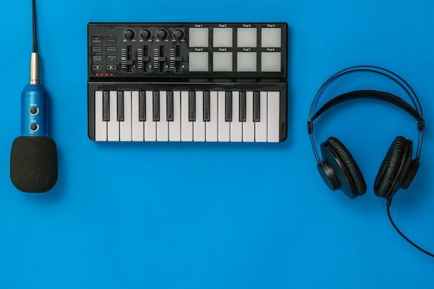 Muziekmixer, microfoon en hoofdtelefoons op blauw