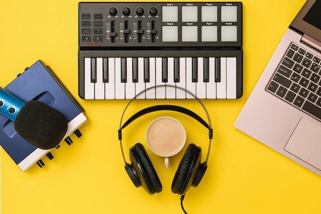 Muziekmixer, microfoon, koptelefoon en geluidskaart op gele achtergrond. het concept van werkplekorganisatie. apparatuur voor het opnemen, communiceren en luisteren naar muziek.