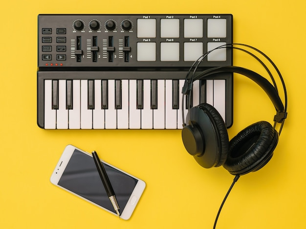 Muziekmixer, smartphone, koptelefoon en pen op gele achtergrond. het concept van werkplekorganisatie. apparatuur voor het opnemen, communiceren en luisteren naar muziek.
