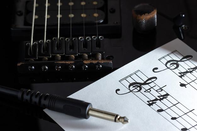 Muzieknoot en jack-kabel op zwarte elektrische gitaar in het donker.