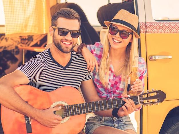Muziekpauze tijdens roadtrip. knappe jongeman die in een minibusje zit en gitaar speelt terwijl zijn vrolijke vriendin zich aan hem hecht en glimlacht