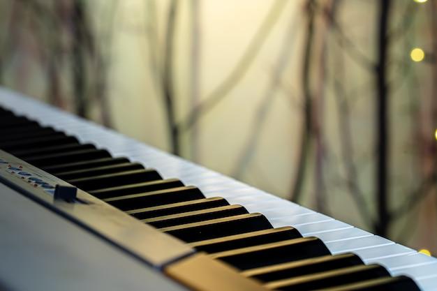 Muziektoetsen onder gekleurde verlichting op een onscherpe achtergrond.