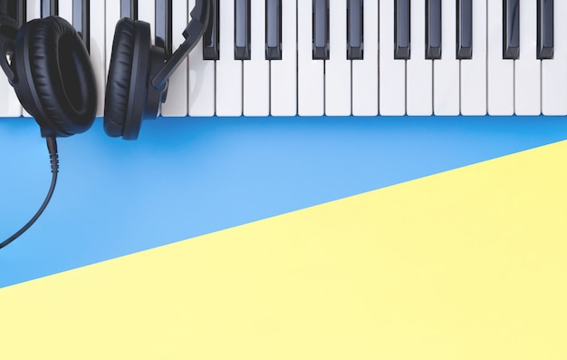 Muziektoetsenbordinstrument met hoofdtelefoon op blauwe gele exemplaarruimte voor muziekconcept