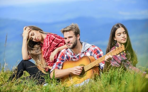 Muzikale pauze. wandelen entertainment. vredige plek. melodie van de natuur. wandeltraditie. vrienden wandelen met muziek. mensen ontspannen op de bergtop terwijl knappe man gitaar speelt. samen zingen.