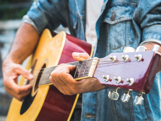 Muzikant die akoestische gitaar op onduidelijk beeldachtergrond speelt