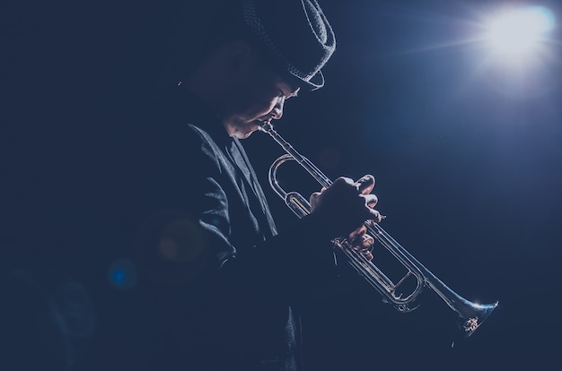 Muzikant die de trompet bespeelt met spotlicht en len-flare op het podium