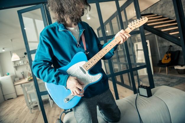 Muzikant die gevoelens uitdrukt. ervaren geïnspireerde man met golvend haar die zijn gitaarvaardigheden traint terwijl hij op zijn knieën staat