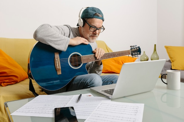 Muzikant die gitaar speelt en muziek componeert met zijn collega's