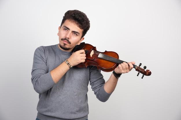 Muzikant die het deuntje van zijn viool controleert en repareert.