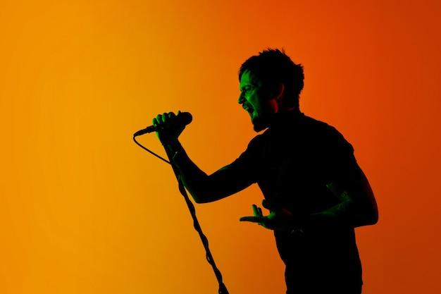 Muzikant geïsoleerd op donkere studio in neonlicht