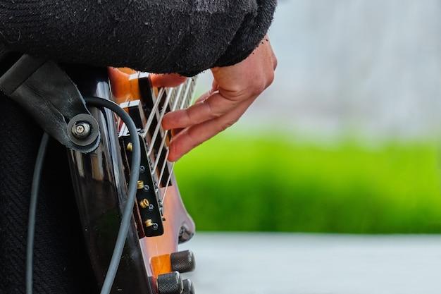 Muzikant houdt een muziekinstrument-gitaar vast en speelt op straat.