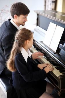 Muzikant leraar traint om piano te spelen, klein meisje